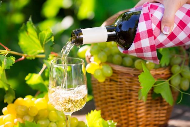 야외에서 유리에 화이트 와인을 붓는
