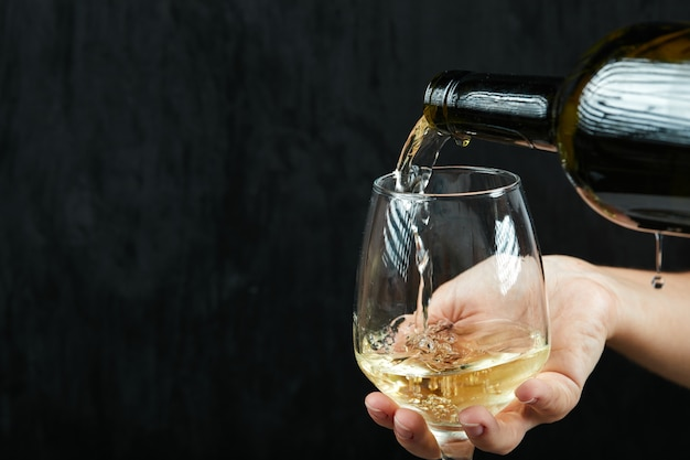 暗い表面のワイングラスに白ワインを注ぐ
