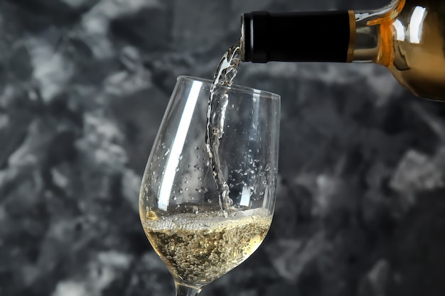 Pouring of wine from bottle into glass on grey surface
