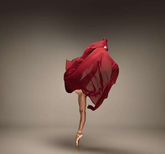Разливное вино. изящная классическая балерина танцует на сером фоне студии. нежная красная ткань. изящество, художник, движение, действие и концепция движения. выглядит невесомо, гибко. модный стиль.