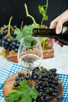 Pouring wine into the glass with plate of grapes on white table