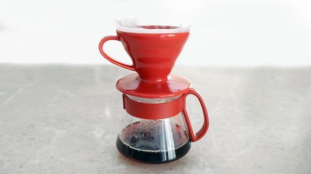 Обдавать. v60. фильтр свежего горячего кофе капает в стеклянный сервиз