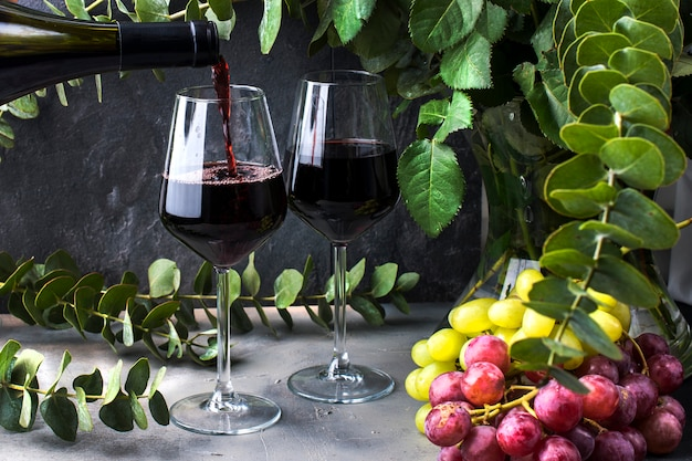 Pours wine from a bottle into a glass, on a black background with red roses and grapes