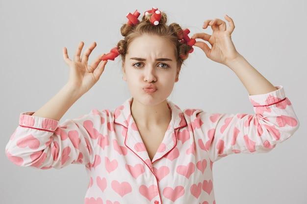ナイトウェアを着て、かわいい10代の女の子の脱毛ヘアカーラーをふくれっ面