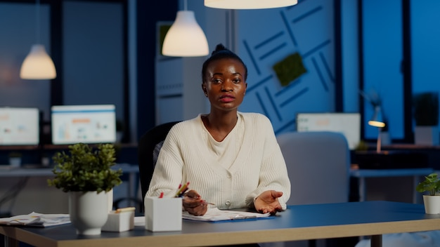 Pov of african businesswoman having video conference with team during midnight looking in camera in workplace. freelancer using wireless technology network talking on virtual meeting doing overtime