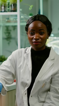 Pov of african woman sitting at desk table in pharmaceutical laboratory during online videocall meeting. specialists team researching genetic mutation developing dna gmo biology test