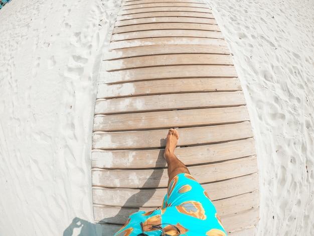 Pov и первый вид человека, гуляющего по белому пляжу и смотрящего на синее море или океан в солнечный день отпуска