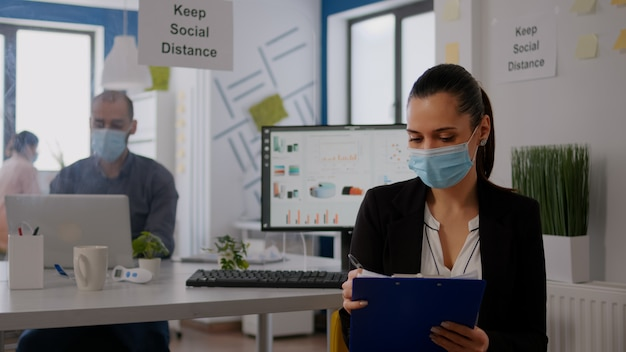 Pov of business woman with medical face mask working at communication project with team during online video conference. entrepreneur on web internet video call in new normal corporate space