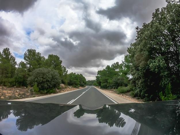 검은 색 낮은 구름이 흩어져있는 무르시아의 국가 전망과 함께 직선 양방향 아스팔트 도로에서 검은 차를 운전하는 pov. 스페인 소나무 숲을지나 가기 위해.