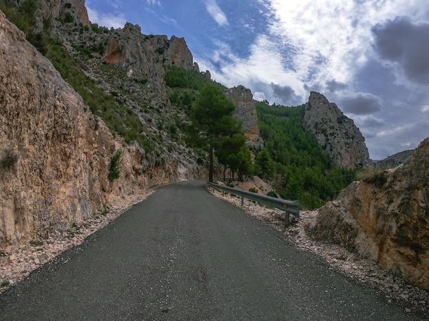 Pov는 절벽과 암벽 사이의 스페인 알바세테의 지중해 소나무를 통해 외로운 오래된 곡선 도로에서 자동차를 운전합니다. 남유럽의 nerpio 도로에서 주행