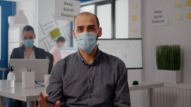 新しい通常のオフィスでのズーム会議の呼び出し中に保護フェイスマスクを持つハメ撮り起業家の男。リモートオンラインビデオ電話会議でカメラに向かって話しているフリーランサー