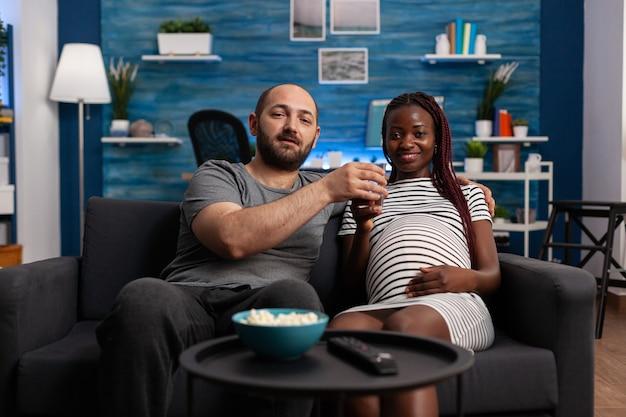 Pov di una coppia interrazziale con una gravidanza che guarda un film