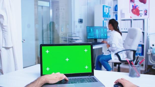 병원 캐비닛에 녹색 모형이 있는 pov 노트북 디스플레이. 개업의가 진료소 유리문을 엽니다. 의료 클리닉에 디스플레이에 크로마 키가 있는 노트북을 사용하는 메딕.