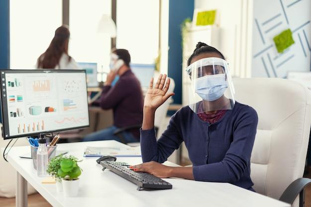 Pov африканского менеджера на рабочем месте, имеющего виртуальный звонок с деловыми людьми в масках в качестве меры предосторожности для covid19. женщина разговаривает с командой во время онлайн-конференции, пока коллеги работают