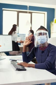 Covid19に対してフェイスマスクを着用して机に座っている職場にリモートコールするアフリカ人労働者のハメ撮り。同僚がバックグラウンドで作業している間、オンライン会議中にチームと話している女性。