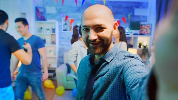 Pov привлекательного лысого мужчины, машущего в камеру во время вечеринки со своими друзьями