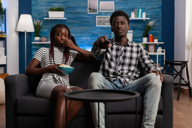 텔레비전을 보고 카메라를 보고 소파에 흑인 부부의 pov. 남자가 집에서 tv 리모컨을 들고 있는 동안 그릇에서 팝콘을 먹는 아프리카계 미국인 여자