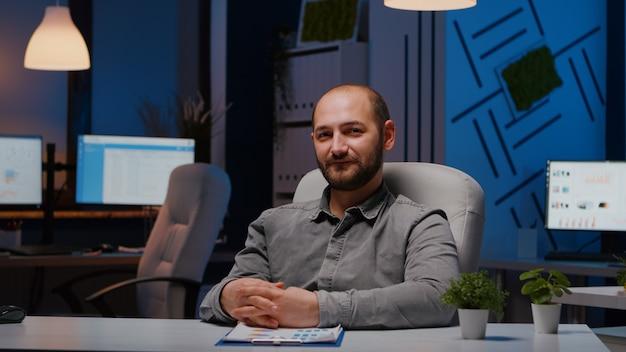 Pov бизнесмена, объясняющего маркетинговый проект во время видеоконференции, посвященной веб-семинару, в офисе стартапа. менеджер мужчина, имеющий деловую работу, собеседование по удаленной работе поздно ночью