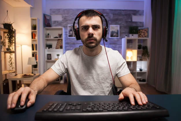 네온 불빛이 있는 방에서 컴퓨터로 온라인 슈팅 게임을 하는 경쟁적인 청년의 모습. 헤드폰을 낀 남자.