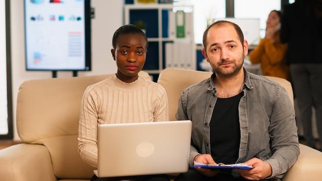 現代のスタートアップオフィスでソファに座って新しいビジネスのために働いているウェブカメラを使用してビデオ会議中に財務戦略について話し合っている多様な同僚のpov。再分析する多民族の同僚