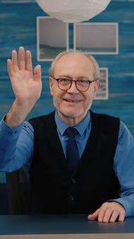 Pov пожилого мужчины машет рукой во время видеоконференции