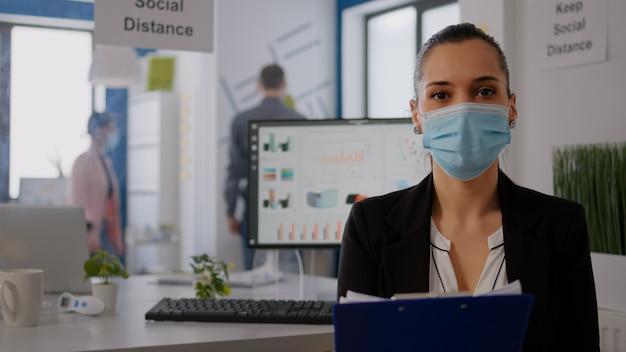 사무실에서 온라인 화상 통화 회의 중에 비즈니스 정보를 작성하면서 팀과 이야기하는 기업가의 pov. 코로나바이러스 감염을 방지하기 위해 보호용 안면 마스크를 착용한 프리랜서