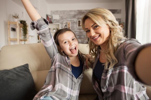 ソファに座っているリビングルームで母親と結合している中かっこを持つ幸せな少女のハメ撮り。