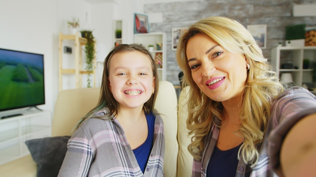 彼女の美しい若い母親の隣に座っているカメラに彼女のブレースを示す少女のハメ撮り。