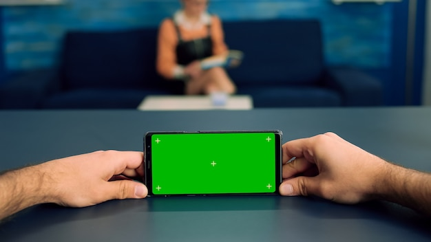 Pov человека, руки, держащие в горизонтальном режиме смартфон с зеленым экраном с цветным ключом, стоящим на столе в офисной студии