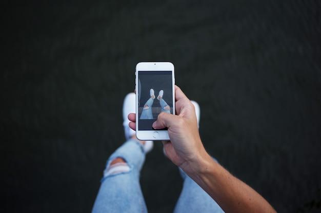 ソーシャルメディアのスマートフォンで白いスニーカーで彼の足と足の写真を作るトレンディなファッショナブルなヒップスタースキニーデニムジーンズの男の視点