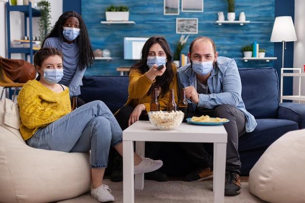Pov многонациональных друзей, использующих пульт от телевизора для переключения канала, сидя на диване в маске для лица во время вспышки пандемии коронавируса в качестве профилактики распространения, весело проводя время.