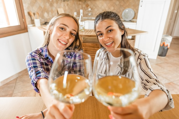 Pov portrait of two girls looking at camera holding champagne glasses in selective focus. students celebrating online with alcohol using video conferencing technology. new normal social activity