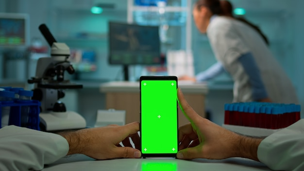 Colpo pov del chimico che utilizza smartphone con schermo verde in laboratorio biologico. operatore medico che indossa camice bianco in clinica che lavora con il cellulare con chiave cromatica su display isolato nel laboratorio medico