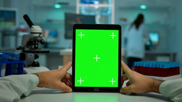 Pov shot of chemist using tablet with green screen in biological laboratory. medical worker wearing white coat in clinic working with notebook with chroma key on isolated display in medical lab