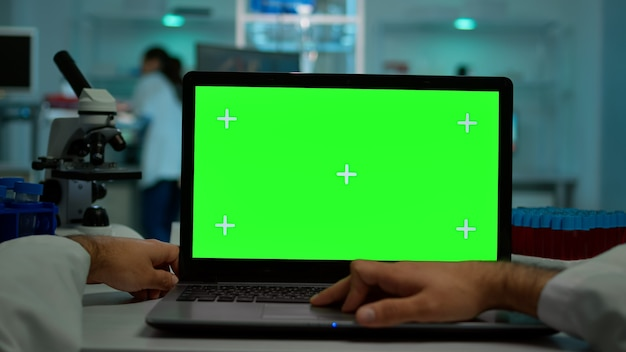 Pov shot of man scientist sitting at desk working on laptop with mock-up green screen, isolated display. in background lab researcher analysing vaccine developent examining samples