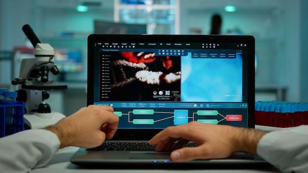 Pov-выстрел биохимика, анализирующего эволюцию вакцины на ноутбуке, сидящего за рабочим столом и изучающего симптомы вируса. в фоновом режиме исследователь лаборатории проверяет и готовит химическую посуду
