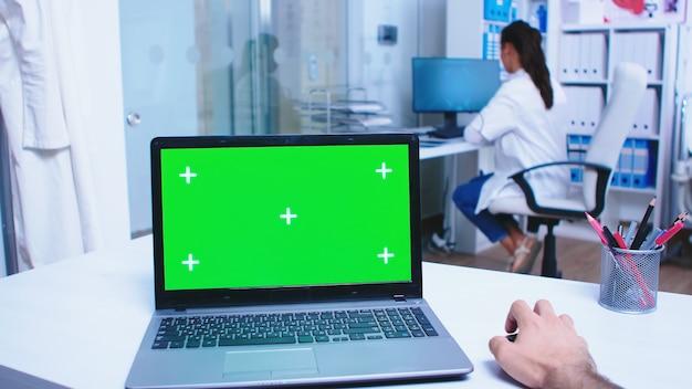 病院のキャビネットで緑色の画面とラップトップを使用して医師の主観的なショット。クリニックで白衣を着た医療従事者。診療所に展示されているクロマキー付きノートを使ったメディック。