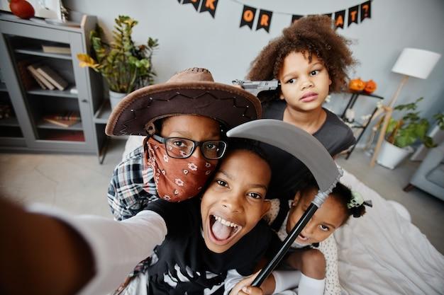 Pov-снимок возбужденных афроамериканских детей, одетых в костюмы на хэллоуин дома и делающих селфи, глядя ...