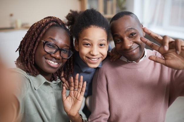 自宅で自分撮り写真を撮ったり、ビデオチャットを使用しているときにカメラに微笑んで幸せなアフリカ系アメリカ人の家族のpovショット