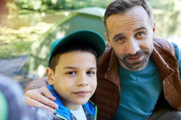 Снимок от первого лица: любящие отец и сын вместе делают селфи во время похода