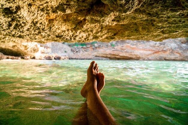 マヨルカのビーチの洞窟の中で身も凍る人の足の主観ショット