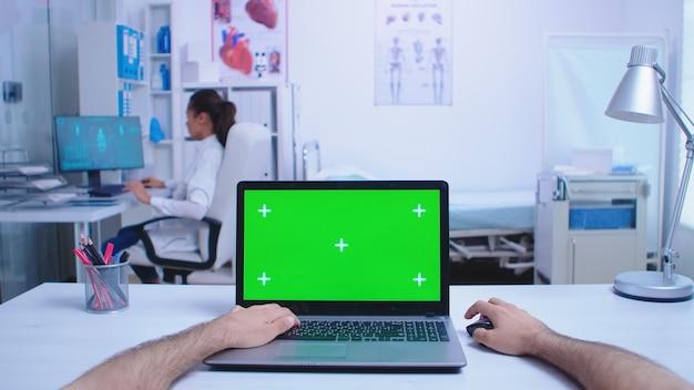 Colpo di punto di vista del medico che utilizza computer portatile con chiave di crominanza nell'armadietto dell'ospedale e medico che esamina l'immagine a raggi x medico utilizzando notebook con schermo verde sul display in clinica medica.