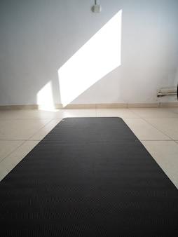 관점 샷. 방 바닥에 펼쳐진 검은색 요가 매트, 흰 벽에 햇빛.