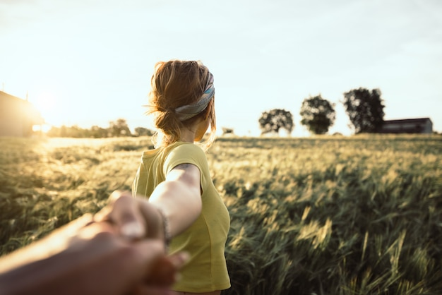 Pov view of a happy young woman holding hand of her boyfriend while walking by a wheat field at sunset. couple enjoying travel in the nature