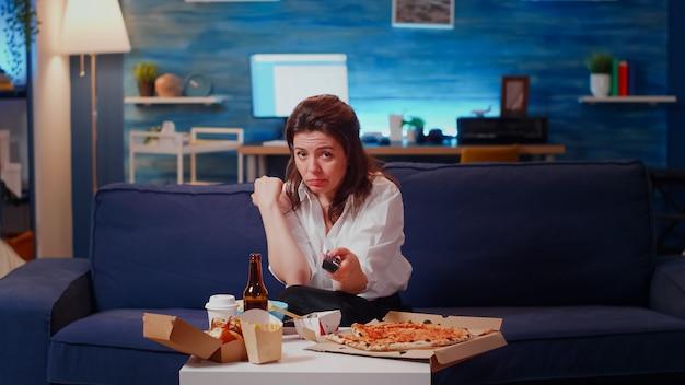 Punto di vista di una donna che cambia canale e mangia patatine