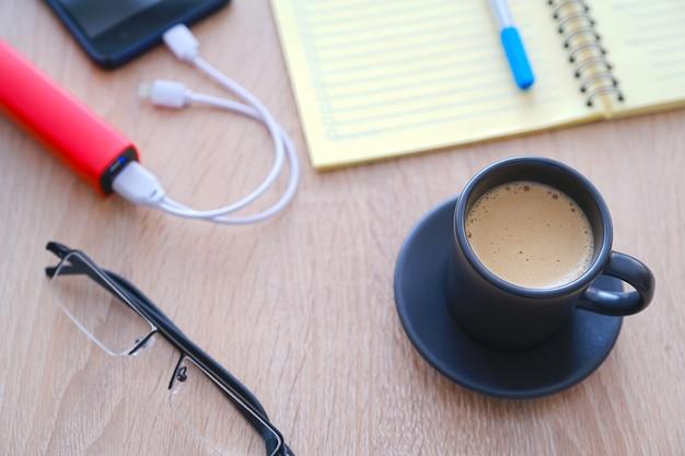 スマートフォンはpoverbankから充電しています。一杯のコーヒー、日記、鉛筆とテーブルの上のグラス