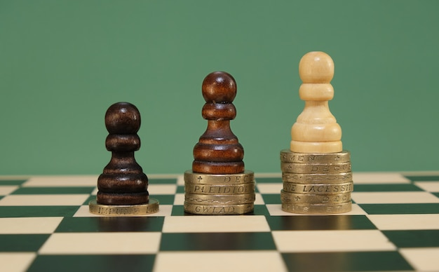 Poverty, wealth and income inequality concept. black, brown and white pawns standing on stacks of coins representing wealth.