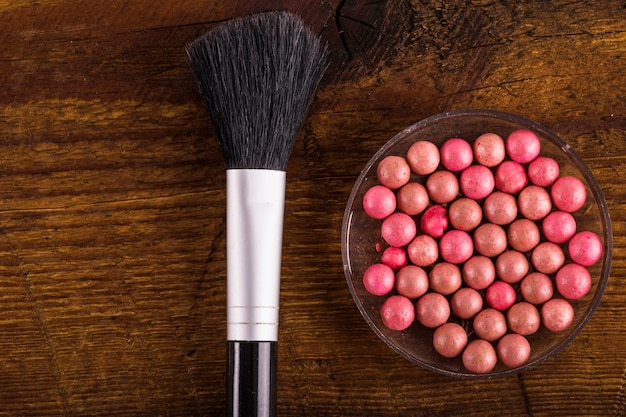 Powder balls and makeup brush on wooden background