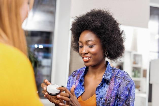 가루. 고객에게 파우더를 보여 주면서 기분 좋은 곱슬 머리의 아름다운 짙은 피부 스타일리스트 프리미엄 사진