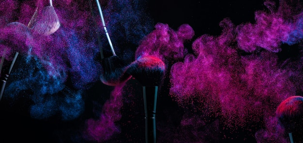 Powder brushes in a cloud of colored shadow pigments.